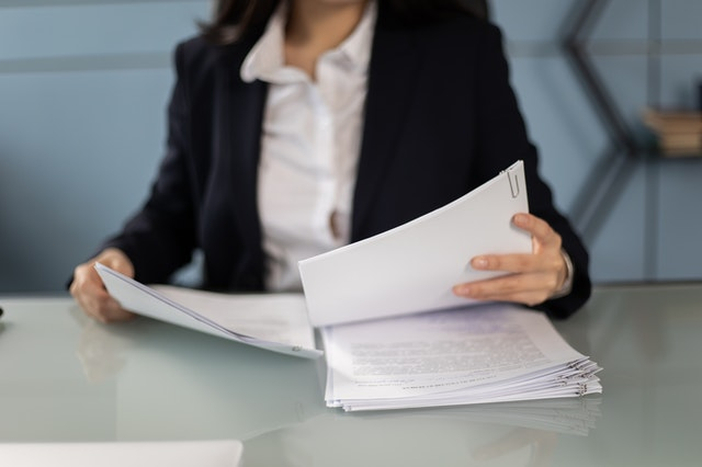 female paralegal reviewing health policy documents before presenting to the audit firms